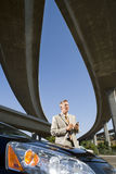Businessman using electronic organiser by car beneath overpasses, low angle view Stock Image