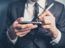 Businessman using electronic pen and smartphone Royalty Free Stock Photo