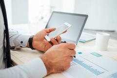 Businessman using a financial app. Businessman at desk using a financial app on his smart phone and working on reports, hands close up Stock Photos