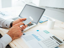 Businessman using a financial app. Businessman at desk using a financial app on his smart phone and working on reports, hands close up Stock Images