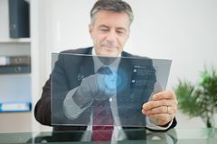 Businessman using futuristic touchscreen to view data Stock Photos