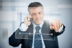 Businessman using futuristic touchscreen to view graph Stock Image