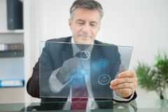 Businessman using futuristic touchscreen to view statistics Stock Photos