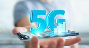 Businessman using 5G network with mobile phone 3D rendering. Businessman on blurred background using 5G network with mobile phone 3D rendering Royalty Free Stock Photo