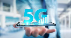 Businessman using 5G network with mobile phone 3D rendering. Businessman on blurred background using 5G network with mobile phone 3D rendering Royalty Free Stock Photos