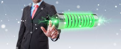 Businessman using green battery with lightnings 3D rendering. Businessman on blurred background using green battery with lightnings 3D rendering Royalty Free Stock Photo