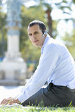 Businessman using hands-free cell phone headset Stock Images