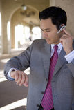 Businessman using hands-free cell phone headset Stock Photo