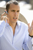 Businessman using hands-free cell phone headset Royalty Free Stock Photos