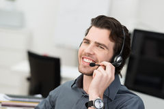 Businessman using a headset. For hands free communication or a young call centre operator taking a call at the help desk Royalty Free Stock Photography