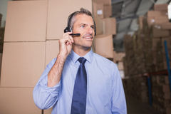 Businessman using headset in warehouse Royalty Free Stock Photo