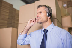 Businessman using headset in warehouse Stock Photos