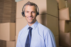 Businessman using headset in warehouse Stock Image