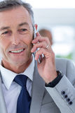 Businessman using her phone with two colleague behind him Stock Images