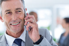 Businessman using her phone with two colleague behind him Royalty Free Stock Image