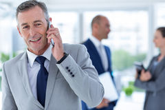Businessman using her phone with two colleague behind him Royalty Free Stock Photos