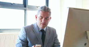 Businessman using his computer and smartphone stock footage