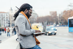 Businessman using his laptop in the Street. Royalty Free Stock Images