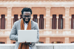 Businessman using his laptop in the Street. Royalty Free Stock Photos
