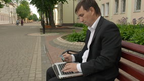 Businessman using his laptop to purchase something online with his credit card. Businessman sitting on a bench in the street using his laptop to purchase stock footage