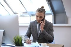 Businessman using his mobile phone in the office royalty free stock image