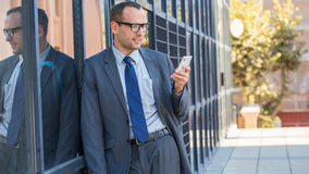 Businessman using his smart phone on a city street. Royalty Free Stock Photography