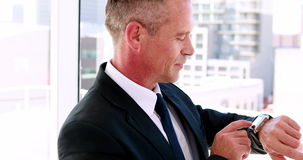 Businessman using his smart watch and smiling at camera stock video footage