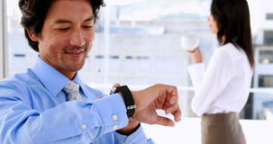 Businessman using his smart watch and smiling stock footage