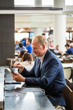 Businessman using his tablet at the airport Royalty Free Stock Photography
