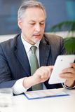 Businessman using his tablet in his office Royalty Free Stock Photography