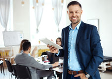 Businessman using his tablet in office Stock Photography