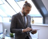 Businessman using his tablet in the office stock images