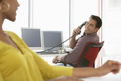 Businessman Using Landline Phone In Office. Happy businessman using landline phone while looking at female colleague Stock Image