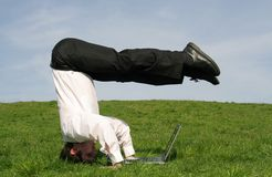 Businessman using laptop. Businessman upside down using laptop Royalty Free Stock Photos