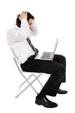 Businessman using laptop. Businessman with laptop, holding head in hands Royalty Free Stock Images