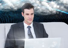 Businessman using laptop against binary codes interface Stock Images