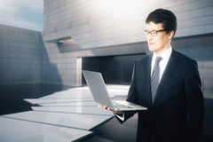Businessman using laptop. Attractive businessman in suit and glasses using laptop on concrete tile exterior background Stock Photo