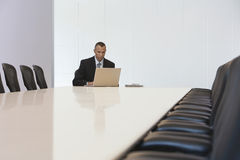 Businessman Using Laptop In Board Room Stock Photography