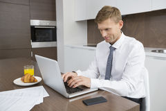 Businessman using laptop at breakfast table Royalty Free Stock Photos