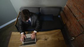 Businessman using laptop in cafe on wood table. top view.  stock footage