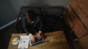 Businessman using laptop in cafe on wood table. top view.  stock video