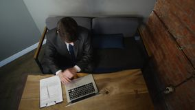Businessman using laptop in cafe on wood table. top view.  stock video footage