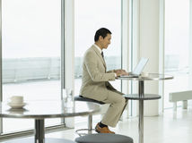 Businessman Using Laptop In Cafeteria Royalty Free Stock Images