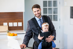 Businessman using laptop while carrying daughter Stock Photos