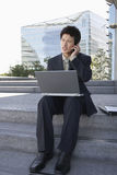 Businessman Using Laptop And Cellphone Outdoors Stock Image