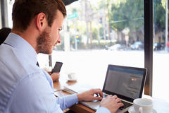 Businessman Using Laptop In Coffee Shop Stock Photo