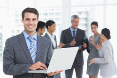 Businessman using laptop with colleagues behind Royalty Free Stock Photos