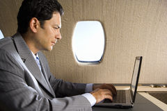 Businessman using laptop computer on aeroplane, close-up, side view Stock Images