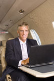 Businessman using laptop computer on aeroplane, smiling, portrait Stock Images