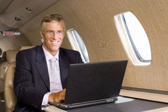 Businessman using laptop computer on aeroplane, smiling, portrait Stock Photos